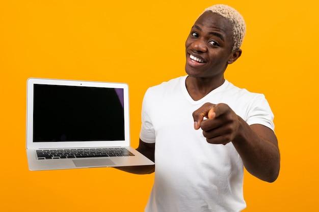 Bel homme africain aux cheveux blancs souriant tenant l'écran d'ordinateur portable en avant tenant le doigt en avant sur jaune