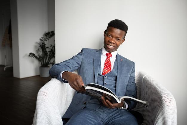 Un bel homme africain en costume au bureau lit un magazine