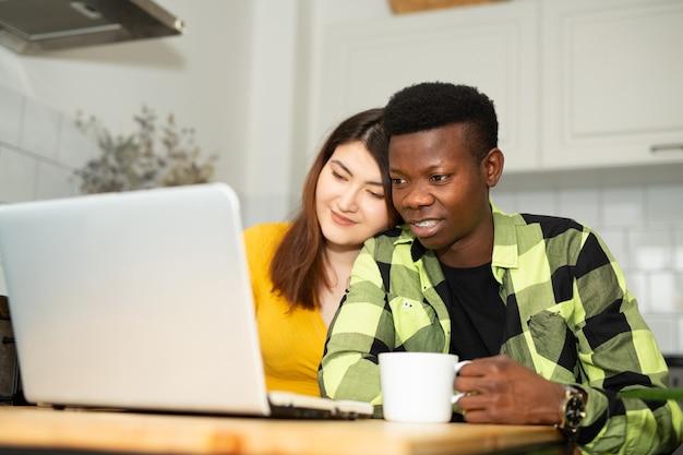 Bel homme africain et femme asiatique dans la cuisine avec ordinateur portable