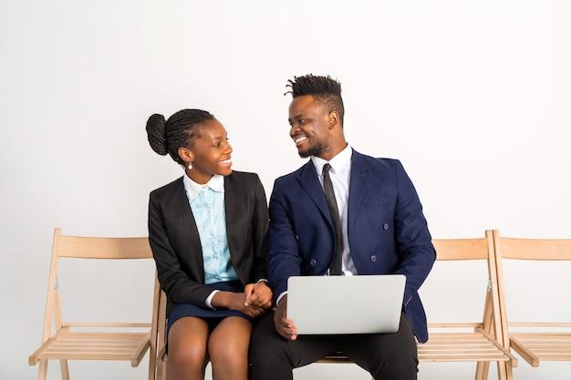 Bel homme africain et femme en costume avec un ordinateur portable