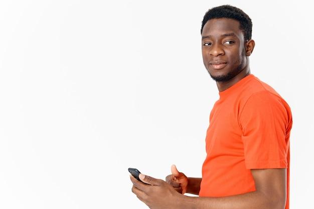 Bel homme africain avec téléphone portable sur fond clair