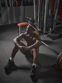 Bel homme afro-américain athlétique musclé assis sur le sol avec haltères en force de gym