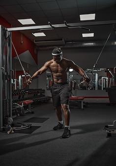 Bel homme afro-américain athlétique musclé exerçant les muscles de la poitrine de formation dans la salle de gym