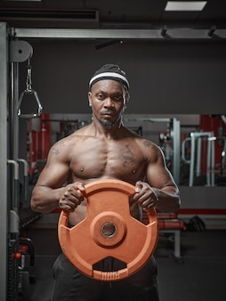 Bel homme afro-américain athlétique musclé exerçant avec une plaque de poids dans la force des mains