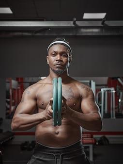 Bel homme afro-américain athlétique musclé exerçant avec des plaques de poids s'entraînant dans une salle de sport