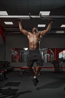 Bel homme afro-américain athlétique musclé faisant des tractions ou des tractions s'exerçant sur l'entraînement en