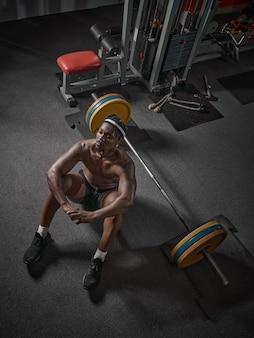 Bel homme afro-américain athlétique musclé reste sur le sol avec haltères en musculation gym