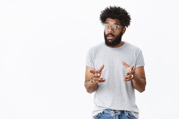 Bel homme afro-américain barbu masculin dans des verres avec des tatouages faisant des gestes et agitant les mains comme parlant, expliquant comment le produit fonctionne en levant les sourcils, décrivant la chose au client