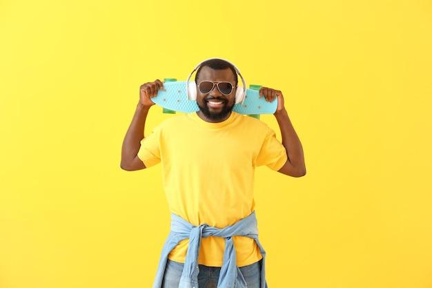 Bel homme afro-américain avec un casque et une planche à roulettes en couleur