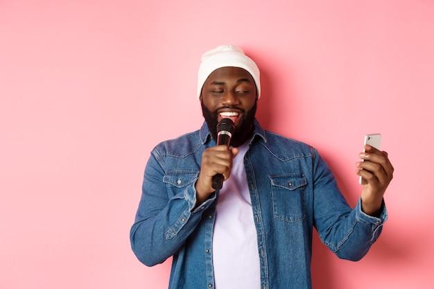 Bel homme afro-américain chantant un karaoké, lisant des paroles sur une application pour smartphone et tenant un microphone, debout sur fond rose