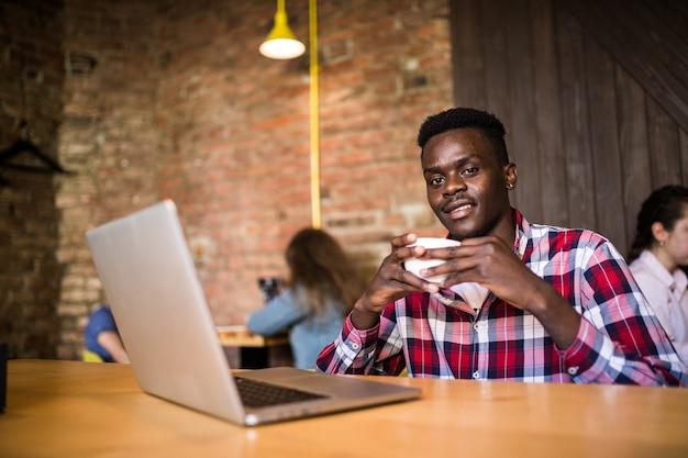 Bel homme afro-américain dans des vêtements décontractés tenant une tasse de café et utilisant un ordinateur portable.