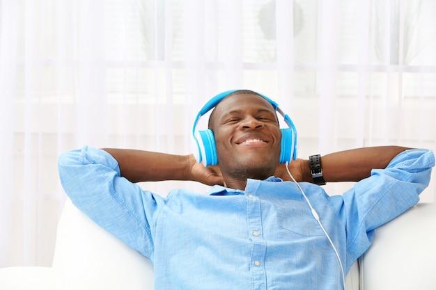 Bel homme afro-américain avec des écouteurs allongé sur le canapé se bouchent