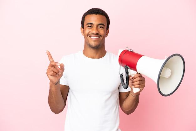 Bel homme afro-américain sur fond rose isolé tenant un mégaphone et pointant vers une excellente idée