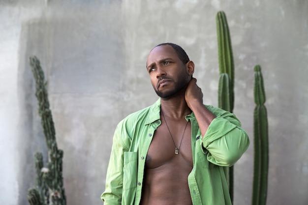 Un bel homme afro-américain joyeux en chemise verte ouverte se tient debout et touche son cou