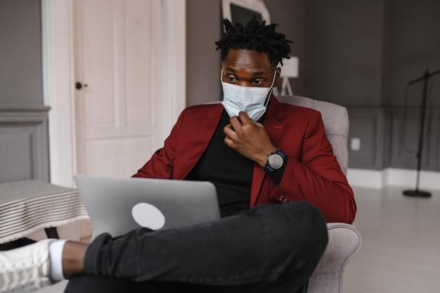 Bel homme afro-américain noir travaillant à domicile et ayant un appel vidéo sur un ordinateur portable tout en étant assis sur un canapé dans le salon.
