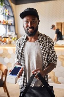 Bel homme afro-américain regardant la caméra et souriant tout en tenant un sac d'emballage thermique isolé et un lecteur de carte sans contact