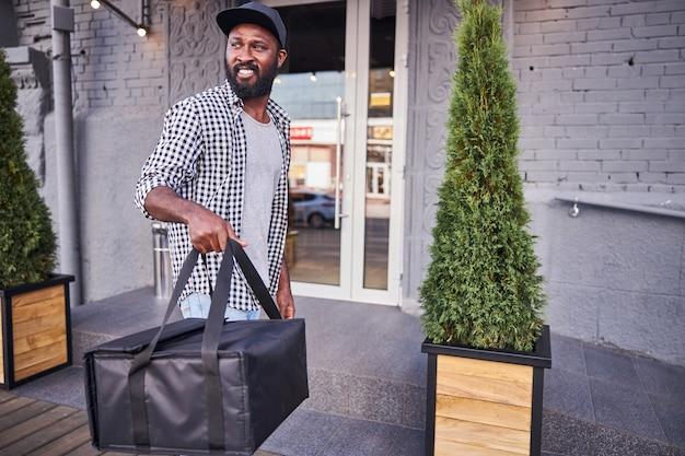 Bel homme afro-américain regardant loin et souriant tout en tenant un sac d'emballage thermique isolé