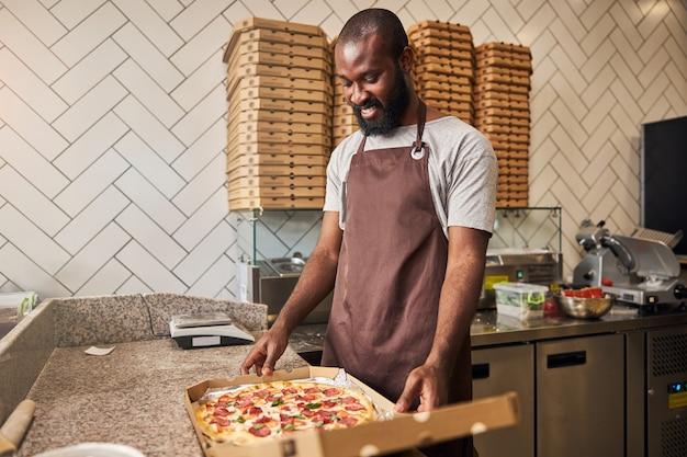 Bel homme afro-américain en tablier regardant une pizza au pepperoni et souriant