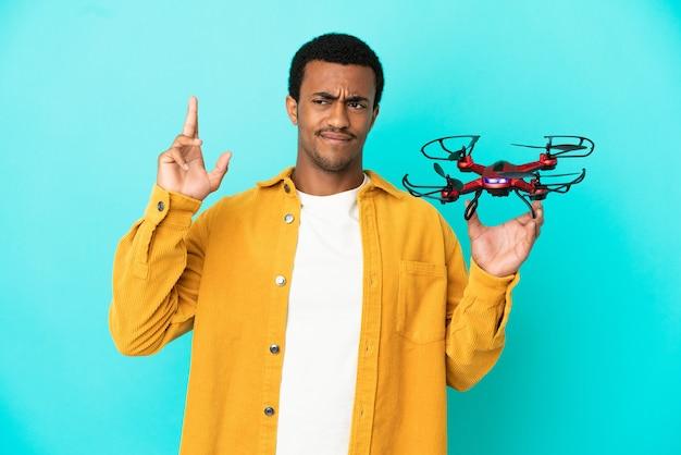 Bel homme afro-américain tenant un drone sur fond bleu isolé avec les doigts croisés et souhaitant le meilleur