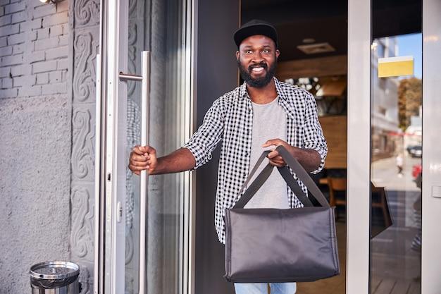 Bel homme afro-américain tenant un sac d'emballage thermique isolé et souriant en quittant la pizzeria