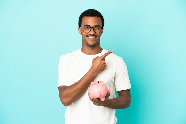 Bel homme afro-américain tenant une tirelire sur fond bleu isolé pointant sur le côté pour présenter un produit