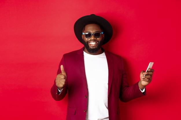 Bel homme afro-américain utilisant l'application téléphonique et montrant le pouce vers le haut, souriant à la caméra, portant des lunettes de soleil et un chapeau fantaisie, fond rouge.