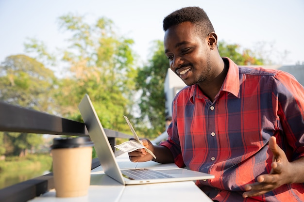 Bel homme afro-américain utilisant un ordinateur portable pour les affaires et le transfert d'argent en ligne ou manuel. concept d'économie de succès.
