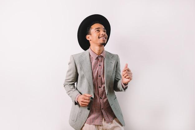 Bel homme afro-américain vêtu d'une veste grise et d'un chapeau noir danse avec un sourire parfait sur fond gris