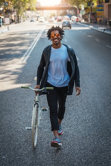 Bel homme afro marchant avec son vélo dans la rue.