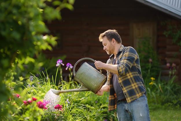 Bel homme d'âge moyen, arrosage des fleurs dans la cour en été.