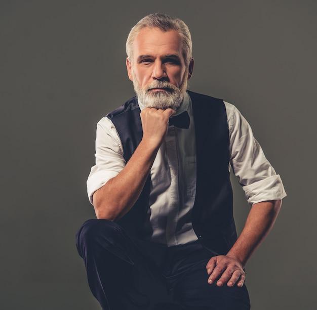 Bel homme d'âge mûr élégant barbu en chemise et noeud papillon.