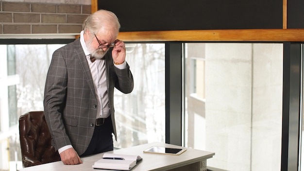 Bel homme d'âge mûr avec des lunettes rentre chez lui après une dure journée de travail