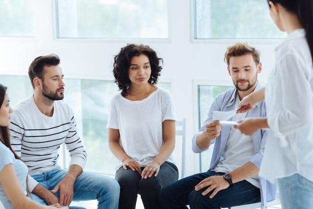 Bel homme agréable et agréable prenant une feuille de papier et se préparant à faire une nouvelle activité psychologique tout en étant assis dans le cercle avec d'autres patients