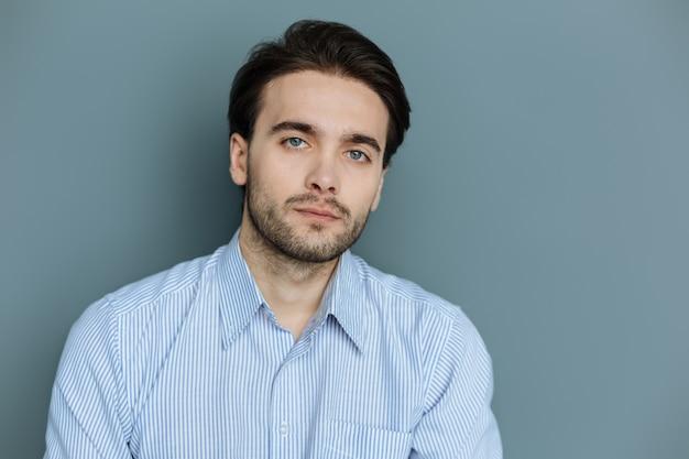 Bel homme. agréable bel homme barbu debout sur fond gris et vous regarde tout en étant sérieux