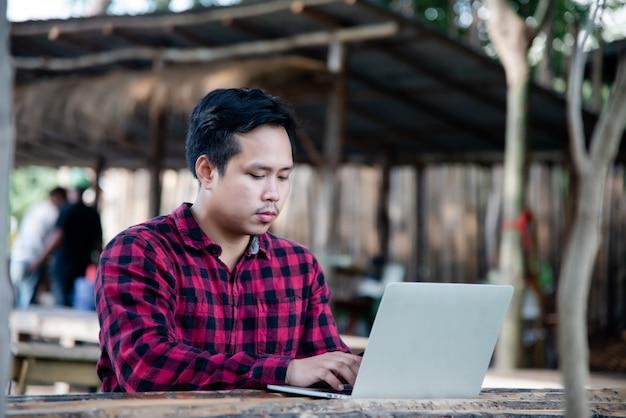 Bel homme à l'aide d'un ordinateur portable dans la nature du voyage