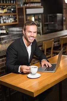 Bel homme à l'aide d'un ordinateur portable et prendre un café