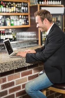 Bel homme à l'aide d'un ordinateur portable