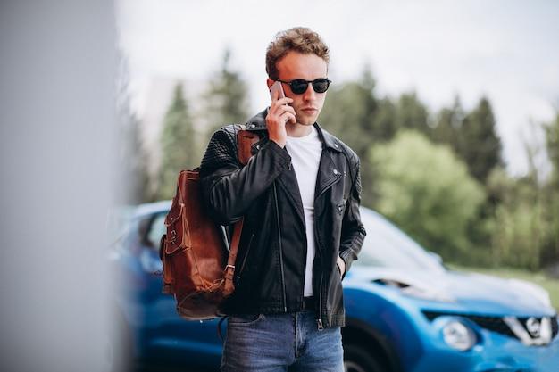 Bel homme à l'aide de téléphone par la voiture