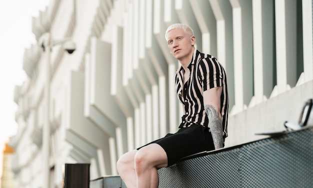 Bel homme albinos assis dans un bâtiment