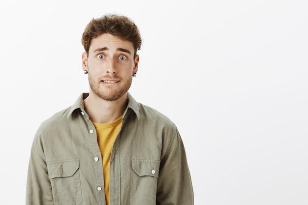 Bel homme anxieux posant dans le studio