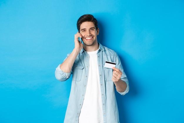 Bel homme appelant la banque et tenant une carte de crédit, ayant une conversation mobile, debout sur fond bleu