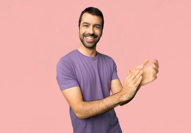 Bel homme applaudissant après présentation lors d'une conférence sur fond rose isolé