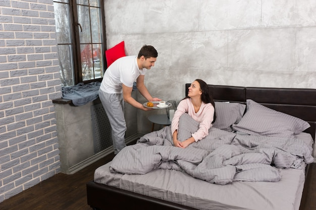 Un bel homme a apporté le petit-déjeuner au lit pendant que sa petite amie se réveillait et était assise dans le lit en pyjama dans la chambre de style loft