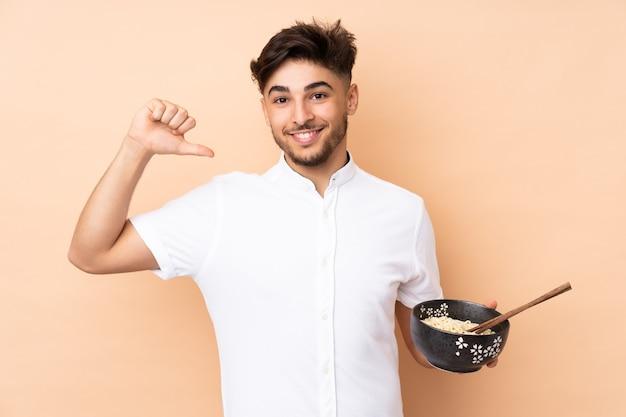 Bel homme arabe isolé sur un mur beige fier et satisfait de soi tout en tenant un bol de nouilles avec des baguettes