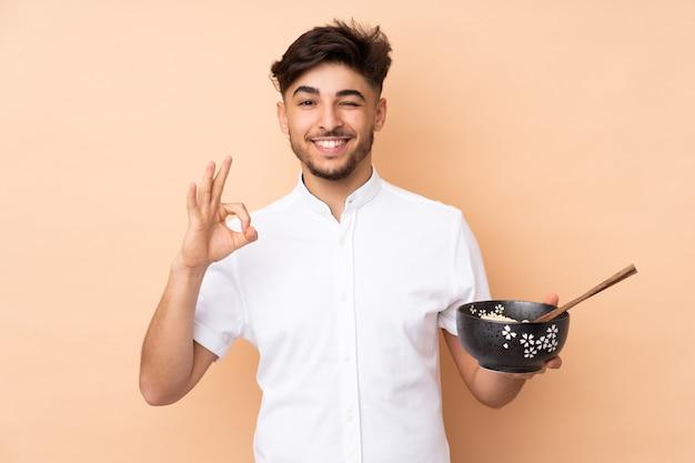 Bel homme arabe isolé sur un mur beige montrant signe ok avec les doigts tout en tenant un bol de nouilles avec des baguettes
