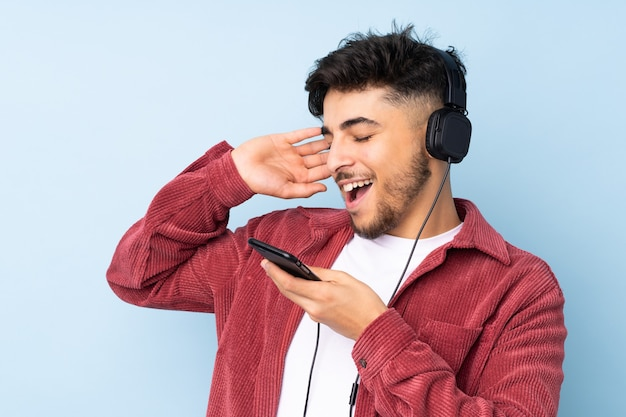 Bel homme arabe isolé sur un mur bleu à l'écoute de la musique avec un mobile et le chant