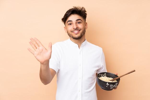 Bel homme arabe sur mur beige saluant avec la main avec une expression heureuse tout en tenant un bol de nouilles avec des baguettes