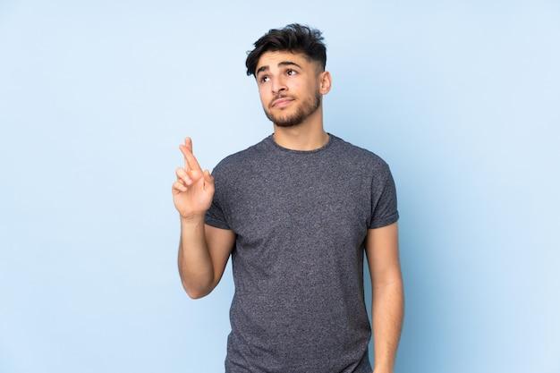 Bel homme arabe sur le mur avec les doigts traversant et souhaitant le meilleur