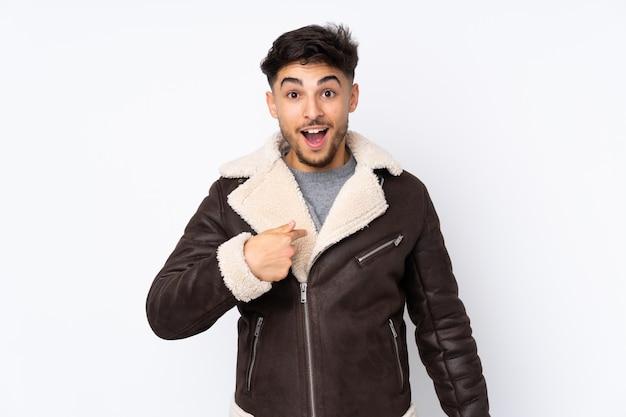 Bel homme arabe sur un mur isolé avec une expression faciale surprise