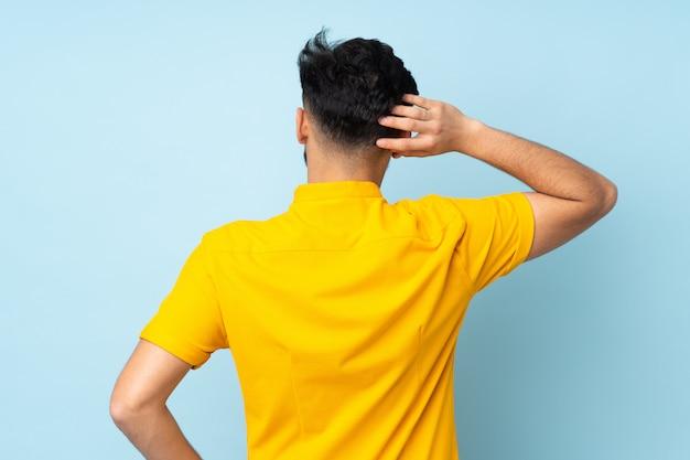 Bel homme arabe sur mur en position arrière et penser
